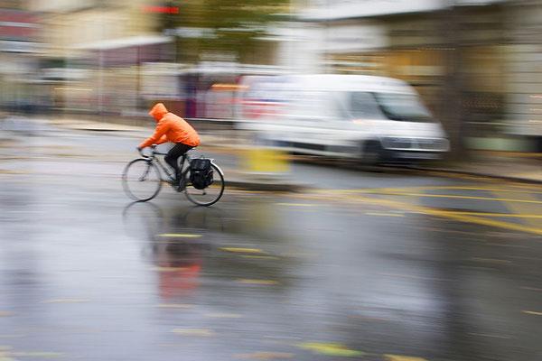 橙色の合羽を着た自転車乗り